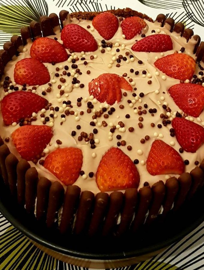 Chocolate and strawberry cake with chocolate finger biscuits edging